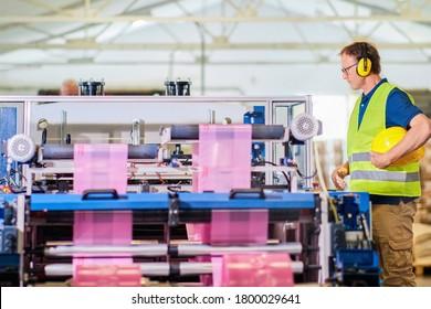 Ingenieur, der an der Herstellung von Plastiktüten arbeitet. Druckmaschine.