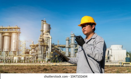 Engineer working at a petrochemical plant or oil and gas refinery plant  with talking on the walkie-talkie for controlling work