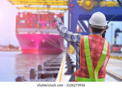 Engineer working at a port with hand holding talking on the walkie-talkie for controlling work in harbor and crane in port loading container.