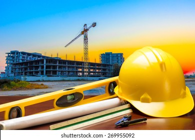 engineer working table plan and blueprint at building construction site against beautiful sky sunset