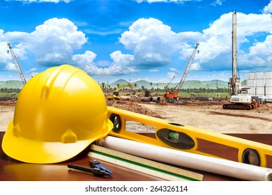 engineer working table plan and blueprints in building construction site against blue sky