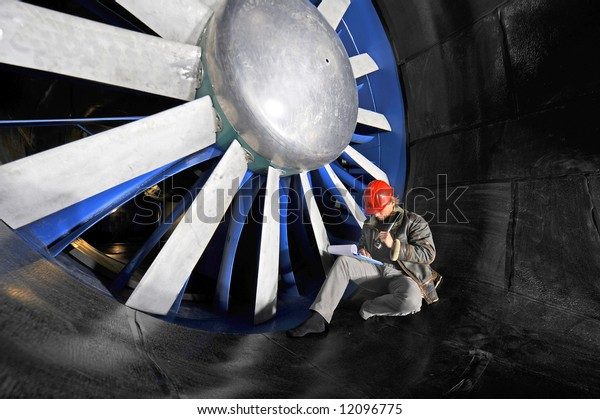 An engineer working through a checklist on a clipboard in front of the huge blades of a wind tunnel