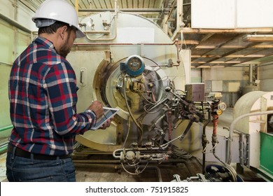 Engineer working using digital tablet near Gas boilers in gas boiler room for steam production of factory industrial manufactured