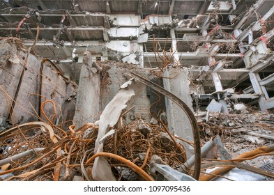 Engineer works for demolition and construction of buildings at industrial site. Reinforcement and concrete under broken houses.