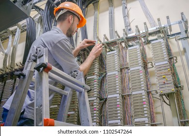 The engineer works in the server room of the data center. Cable laying in telephone exchange. A worker standing on the stairs commutes telephone wires.