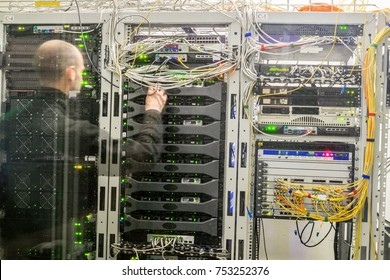 The engineer works in the server room. A man is behind a glass datacenter wall. Modern computer equipment is in server racks. Selective focus