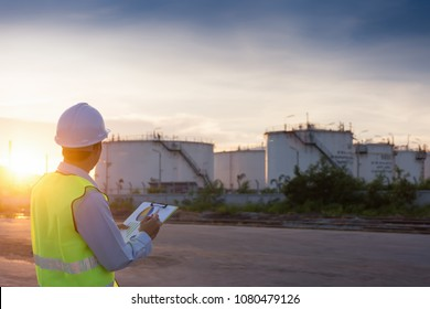 Engineer writing on the paper in front of the oil tank.Refinery, gas and oil