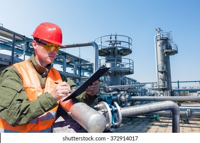 Engineer writing on the paper in front of the natural gas pipes.Refinery, gas and oil