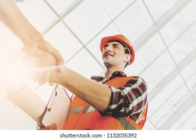Engineer in Yellow Helmet and Vest Greeted Man with Warm Handshake. Modern Construction and Engineering Concepts. Safety of Work in Production and Construction. Hard Work on Project.