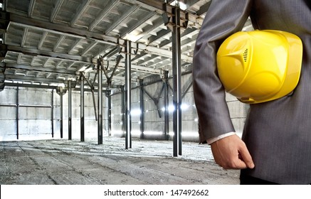 engineer yellow helmet for workers security against the support beams of the unfinished industrial workshop or room inside   Copy space for inscription