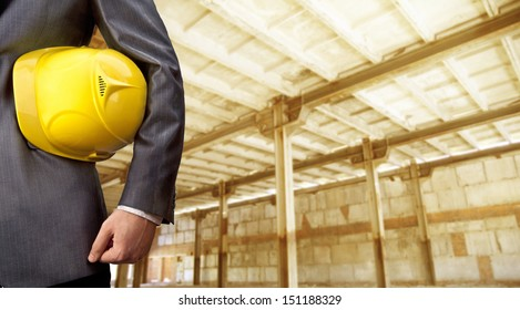 engineer yellow helmet for workers security on background empty brown warenhouse with metal pillars of  Copy Space for inscription