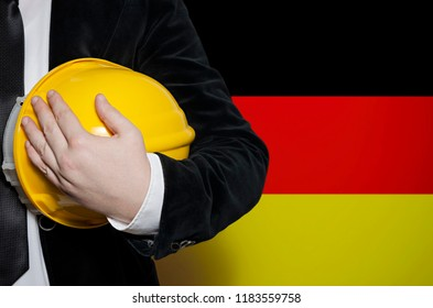 Engineer with yellow plastic helmet on a Germany flag background