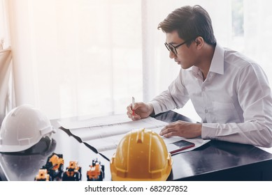 Engineer young man has been working on the design of a building on a desk with a safty hat in the office. Workspaces with drawing buildings, mobile phone, safty hats are white and yellow, on the desk.
