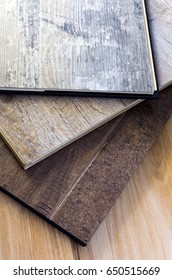engineered hardwood and vinyl floor planks of various styles and finishes in a stack