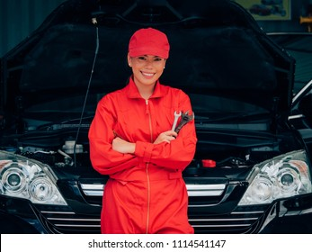 Engineering Asain woman fixing car.