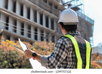 Engineering Consulting People on construction site holding blueprint in his hand. Building inspector. Construction site check drawing and business workflow of new highrise building.