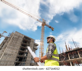 Engineering Consulting people on construction site holding blueprint in his hand. Building  inspector. Construction site check drawing and business workflow of new building