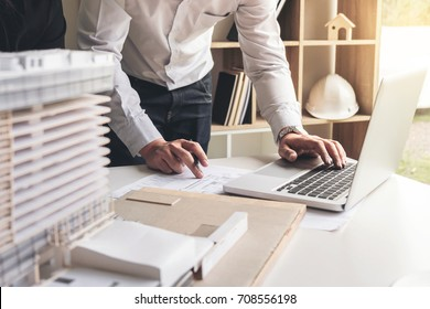 Engineering or Creative architect in construction project, Engineers hands working on construction blueprint and building model at a workplace in office, Building and architecture concept.