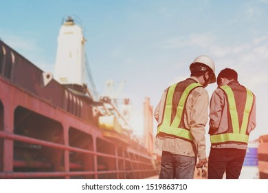 Engineering foreman, worker on main deck of cargo ship wearing safey helmet near cargo hold on board planing and check stork for loading product import export in port and security method