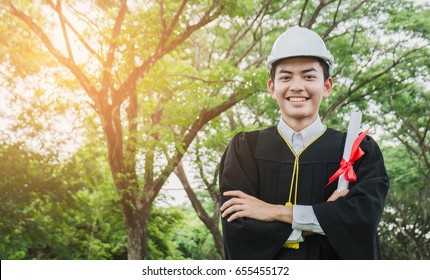 Engineering graduated students holding a diploma and wearing a helmet, smiling happily.