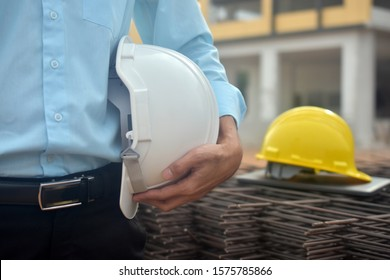 Engineering hold safety hard hat work building construction,Project Engineer holding helmet building estate background
