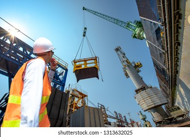 engineering, loading master connecting with gantry crane driver by walkie talkie for lifting safety operation in loading the goods or shipment