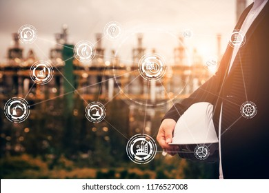 engineering man with safety helmet standing at smart factory background against oil refinery plant in heavy petrochemical industrial estate