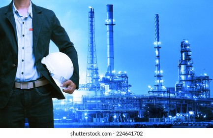 engineering man and safety helmet standing against oil refinery plant in heavy petrochemical industry estate