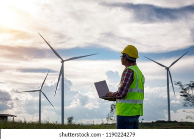 Engineering man standing holding laptop looking wind turbines clean energy project for produce electricity and checking wind direction.