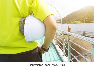 Engineering man standing with white safety helmet, natural golden sunlight at background.