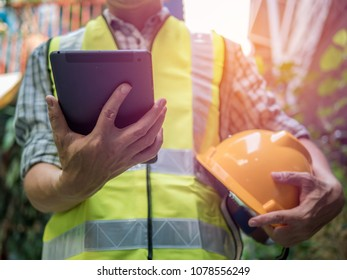 Engineering man standing with yellow safety helmet and holding tablet, work concept