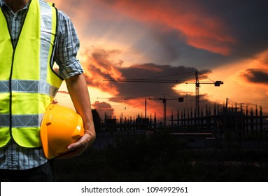 Engineering man standing with yellow safety helmet and construction site with cranes in sunset background, overtime