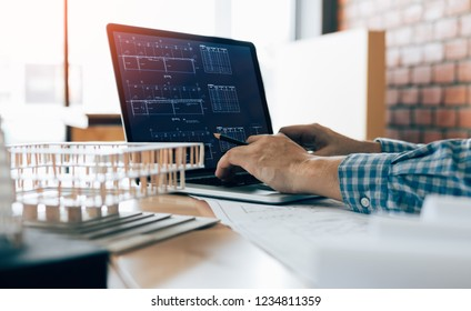 Engineering man using laptop and sitting in modern office working blueprint project.