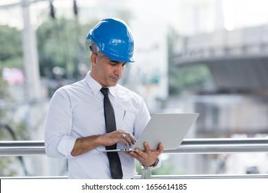 Engineering man wear blue helmet working with laptop outdoor building office.