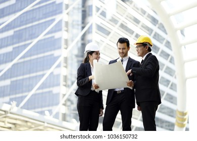 Engineering man and woman with paper and hardhat working outdoor . Team of architects working together on business plan. Work group of three developers collaborating on construction site.