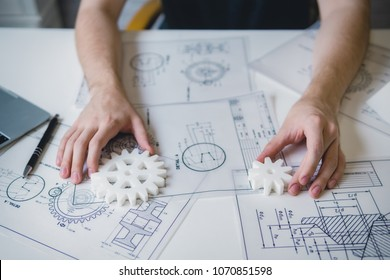 Engineering man's hand working with 3D printer's components and blueprint for designing mechanical parts . Engineering tools and  technology concept.