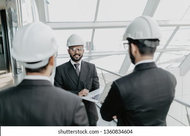 Engineering men with paper and hardhat working indoors in building . Team of architects working together on business plan. Work group of three developers collaborating on construction site.
