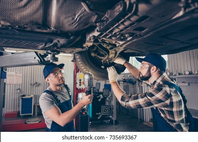 Engineering, protection, reliability, safety, oneness, colleagues, assistance. Professionals in blue overalls, protective spectacles are examining changing tires, tyres, brake pads at work shop