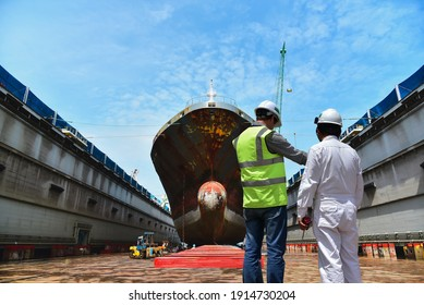 Engineering Shipyard working in dry dock yard The bulk carrier general cargo ship in dry dock yard, recondition of hull repairing and repainting,