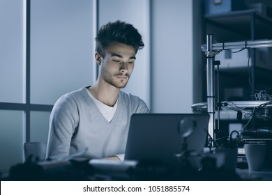 Engineering student working at night in the lab with a laptop, 3D printer in the background