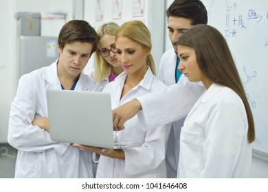Engineering students meeting and discussing ideas in the laboratory, a student is writing on a whiteboard