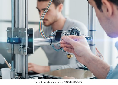 Engineering students using an innovative 3D printer in the laboratory
