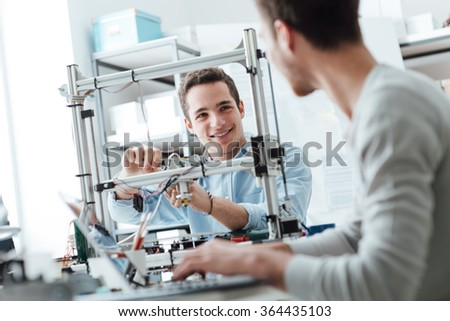 Engineering students working in the lab, a student is adjusting a 3D printer's components, the other one on foreground is using a laptop