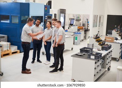 Engineering Team Meeting On Factory Floor Of Busy Workshop