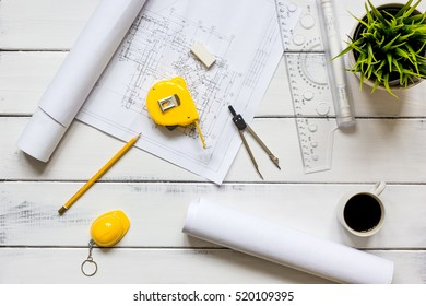 engineering tools on wooden table with drawings apartments top view