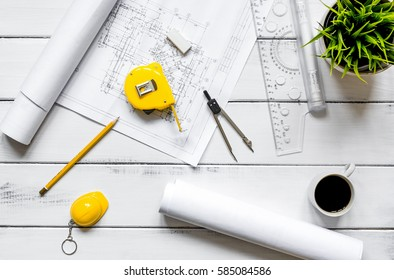 engineering tools on wooden table with drawings apartments top v