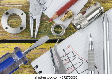 Engineering tools and sketches on the yellow wooden work table for electrical engineering project