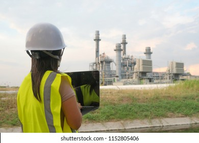 Engineering women are checking oil refineries and gas stations on notebooks. In the industrial area.