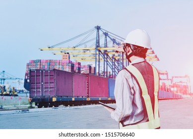 Engineering worker check with tablet in hand and pointing wearing safety helmet hard hat in port on container on train and crane in port background import export shipping concept business retro tone