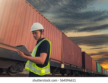 Engineering working hold tablet in front of cargo loading workplace, Freight train